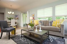 Drew and Jonathan kept the room mostly neutral with a coat of gray paint and a new tan sofa, but they brought in fun accent pieces, such as the yellow throw pillows and floral area rug to liven up the space.