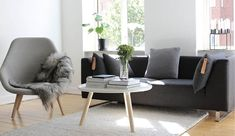 salon blanc aménagé avec un canapé gris graphite, un fauteuil en bois clair et gris clair et une table basse en bois et blanc