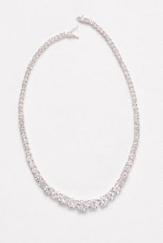 Sparkling cubic zirconia solitaires increase in scale as they make their way along this gleaming necklace.   Cubic zirconia, brass, rhodium  Hinge clasp  16 L  Imported
