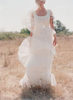 """Viola is a playful and whimsical dress perfect for the bride wanting something unique and vintage inspired. The 100% silk organza layers are gathered and hand crinkled for a distressed look. No two will look identical.  Silk organza shell Fully lined, polyester Velvet sleeve trim color customizable Made in the U.S.A. Available in off-white  Model is 5'10"""" in height, measurements are 34, 25, 36"""" and she is wearing a size 4 Photo credits: Elizabeth Messina"""