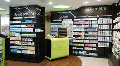 Aménagement d'une pharmacie design avec des rayonnages sur fond noir et des comptoirs vert pomme