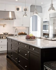 Beautiful kitchen! White cabinets, black island, White Carrera marble!