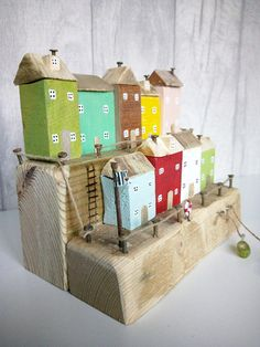 Made from driftwood, reclaimed wood and old metal, this Coastal Cottage Scene features nine brightly coloured cottages, with attic roofs and rusting chimneys, split over two levels. Rusting harbour posts surround both rows of cottages, and the piece includes a lifebuoy, flag pole