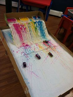 "Explore mark making and colour by racing vehicles through the paint. I did this with cars on our old slide. Encouraged more boys to ""paint"" that day :)"
