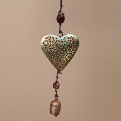 This dainty mobile heart is a great accent piece for your home. The heart has an intricate filigree design and dangling bell. Made from recycled iron, glass beads and NANA bells, this charming mobile