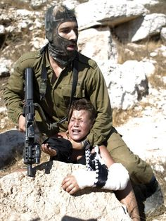 An Israeli soldier holds an injured Palestinian child against a rock, what a hero!!