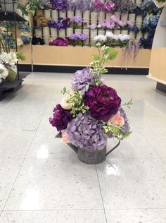 Purple hydrangea and peonies in a water can arrangement
