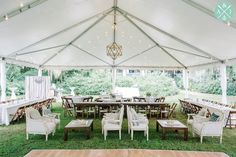 Farm tables, lounge furniture and wood chandeliers under a tented wedding reception at a Magnolia Plantation Veranda wedding planned by Sweetgrass Social // Aaron and Jillian Photography » Husband and Wife International Engagement & Wedding Photographers based in Charleston, South Carolina.