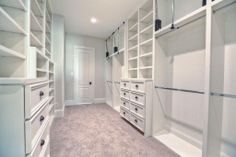 Master Bedroom Closet with access to utility room has custom built cabinetry with pull down hanging metal rods, built in dresser drawers and...
