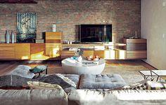 Diante da parede com tijolos, um aparador alongado apresenta diferentes madeiras e volumes, projetado pela arquiteta Fabiana Avanzi. Ela assina a decoração da sala ampla, iluminada e moderna