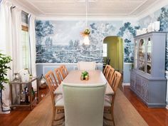 Designer Meg Caswell brings contemporary flair to a turn-of-the-century dining room while still honoring the past. She keeps the original tin ceiling and adds classic elements, like wainscoting. The true showpiece of the space is a breathtaking monochromatic, blue-gray landscape mural.