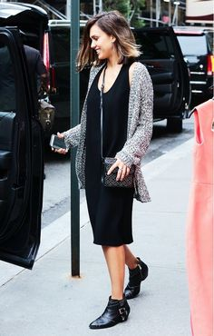 Jessica Alba wears a black tank dress, gray sweater, black studded booties, and a mini black crossbody bag