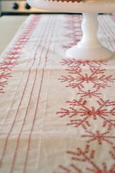 Super cute linen table runner with embroidered red snowflakes.  Christmas 2012?  #weeklongsewingproject