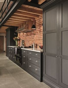 Love the tall plain units against the brick wall, so utility! The extra large stainless steel cooker hood looks perfect. #industrial #industrialkitchen