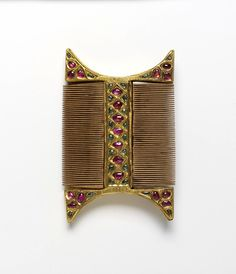 This double-sided, wooden comb is mounted with gold and inlaid with a trellis-work of uncut rubies and emeralds in typically Burmese style. The comb would have been one of the items in a Burmese court lady's cosmetic box known as a bi-it together with oil, perfumes, a few tresses of hair and thanahka (powder).    This comb is believed to be of royal provenance as the strict sumptuary laws of the Burmese court restricted the use of precious stones. circa 1777-1800