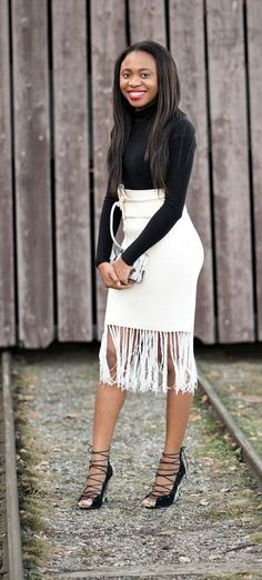 She completely nailed this fringe skirt look. Definitely a stylish way to rock the fringe trend with a wrap belt and fitted turtle neck top. | Knit fringe skirt | Boho style | Summer fashion | White fringe skirt | Skirt outfit idea | Boho fashion