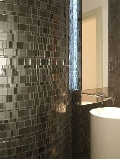 This bathroom has a glass mosaic called Liberty Onyx. There are other metallic colors available including bronzite,diamond, opal, amber,pearl and non metallic colors like red,honey,blue, black, green and grey..
