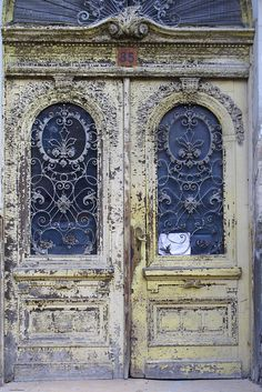 The ornate iron grilles look like lace on these pale yellow doors in Ukraine.
