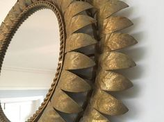 This is a stunning example of a Spanish Gilt Metal mirror made in the 1950s.  An unusual two tiered design features a leaf motif and a rope patterned border.  Good vintage condition - shows some age with use, however this adds to its rich colour and texture.  There is some old wiring on the back when it may have originally lit up. I have left this as is at the moment but I am able to rewire at an additional cost.  Dimensions: Diameter 59 cms/23.25 inches Mirror diameter 33 cms/13 in...