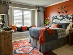 This bedroom utilizes two types of window treatments — the plantation shutters control the flow of light into the room while blending into the window design, while the silver gray curtains give the room a masculine guise with the double row of stripes replicating the lines in the plaid bedding.