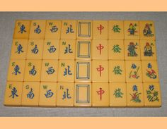 Vintage Mah Jongg tiles: Winds, Dragons, Flowers/People. Most likely made by TYL Manufacturing located in New York, in the '30s & '40s. Their sets are easy to spot because the Flower tiles are in bouquets without numbers, and the paint is usually bright and vibrant. Note the Blue ink.