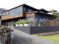 This mid-eighties brick house has been transformed into a very modern looking building. Brick, Garage Doors, Urban, Mansions, House Styles, Building, Outdoor Decor, Modern, Design
