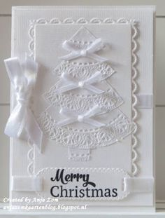 handmade Christmas card from Anja Zom kaartenblog ... all white ... diecuts and ribbon .. luv the tree ... looks like tiers/wedges cut from doily with lacy wide border ...