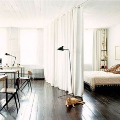 I think the draped curtains works well as a room divider here because the room is so spacious and simple decorated //