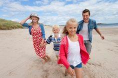 Portrait of smiling family walking on beach Stock Photo