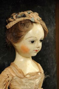 """17"""" tall. Perhaps one of the finest wooden dolls to come to the market! It is quite rare to find such an early doll as this example in untouched as found condition. This doll had previously been in a private collection for many years having been purchased in England in the early 1980`s. Accompanying this doll is an oil portrait purportedly to be of the child to whom the doll belonged. The doll itself is simply amazing! Circa 1720, this fine early styled Queen Anne has glass eyes with a…"""