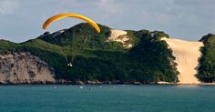 Praticante de parapente sobrevoa a praia de Ponta Negra, a mais turística de Natal (RN). Ao fundo, o Morro do Careca, cartão postal da capital potiguar