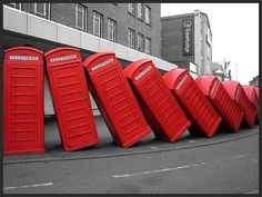 """The famous 'Toppling Telephone Boxes' in Kingston upon Thames in southwest London (historically in Surrey). [Photo by ~Flumpster~ December 21 2008]~[Info about this Landmark- """"One of the more unusual sights in Kingston is several disused red telephone boxes that have been tipped up to lean against one another in an arrangement resembling dominoes. This sculpture by ~David Mach~ was commissioned in 1988 as part of the landscaping for the new Relief Road, and is called """"Out of Order.""""]"""