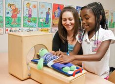 A Child Life specialist is showing a young girl how a medical procedure (a CAT Scan) is preformed by using a doll as visual aid. The goal of this is to show her how the procedure is done so she will be a little more comfortable when having to have it done.
