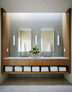 In this modern bathroom, grey tiles have been combined with wood cabinetry that has an open shelf for towel storage. #BathroomDesign #ModernBathroom #WoodVanity #GreyTiles