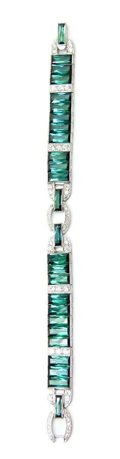 Art Deco green tourmaline and diamond strap bracelet by Cartier, c.1935,   the row of rectangular cut tourmalines divided at intervals by lines of diamonds, an oval diamond and arch motif to centre and forming the clasp