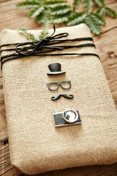 Hipster Christmas gift wrapped in burlap with hat, glasses, moustache, and camera