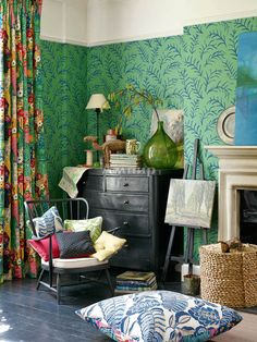 Bloomsbury style. Easel and large painting over mantle, dresser in living area colorful accents and oversized accessories