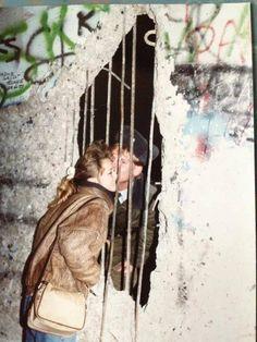 Un bacio scambiato attraverso una fessura del muro di Berlino.