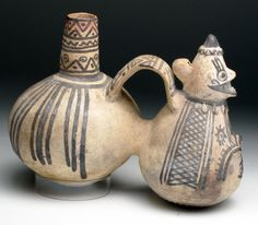 """Peru, Central Coast, Ca 800 to 1100 CE. A truly fabulous pottery whistling vessel. Twin lobed jar, each with deep brown pigment over buff base, front half in the form of a seated figure wearing decorated poncho, arms and knees in relief, conical head with small cap. Reverse is a globular jar (impressed with triple fish scene), spout emerging from top and acts as the mouthpiece to the whistle which is nestled into back of the man's head - and makes a sweet tone. 9-1/4"""" L by 7"""" H."""