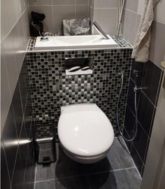Modern wall hung toilet with built in sink in the top of toilet and bidet shower spray