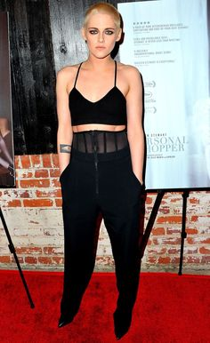 Kristen Stewart (with her new blonde shaved head!) in a black crop top and high-waisted pants