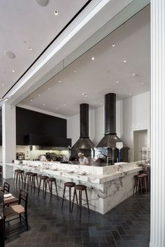 Selldorf's team installed a custom pizza bar for Marta out of Breccia Capria marble. The ovens are tiled in blackened glossy solid glazed brick by Waterworks; the wall behind is clad in Sugar White Glazed Brick by Nemo Tile.