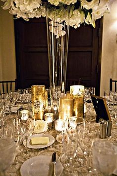 Tall glass centerpieces (only with baby's breath) and small gold mercury glass candles at the base