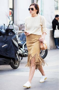 Danielle Bernstein of We Wore What in a neutral look featured a suede fringe skirt