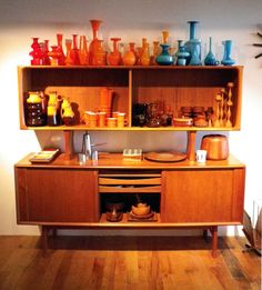 Love the collection of vases - especially the combo of orange and turquoise and the mid-century console is so cool!