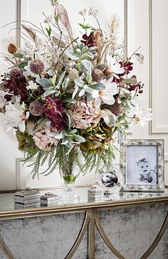 The lush, handcrafted Holiday Splendor Arrangement is brimming with beautiful faux blush-colored blooms. Glitter leaves, peacock feathers and sticks accent the mix of Lamb's-ear, ivory magnolia, orchid and hydrangea flowers in this festive bouquet.