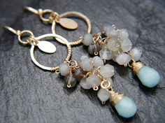 Elegant and playful A long, vine-like cluster of faceted ombre moonstone gemstone beads are looped by hand and dangle from a small circle of hand hammered gold. A 14K gold filled oval charm is framed in the center, while a petite aqua amazonite gemstone hangs from the end of each