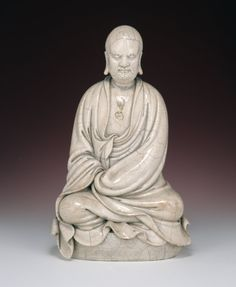 'Blanc de chine' figure of a Bodhidharma with crackled glaze. This figure represents the legendary founder of Buddhism, Bodhidharma, seated cross-legged on an oval dais in meditation with his eyes closed. He is dressed in monastic robes and is identified by his prominent curly eyebrows, whiskers and beard, which are suggested by incised lines.       Ming dynasty 1600-1644 (circa)