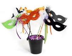 table decoration - Mardi Gras - masks on a stick, stuck into a weighted container - now that's easy.  Add some curled ribbons for extra texture and color.