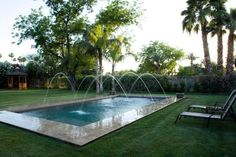 Backyard pool with arching water feature.